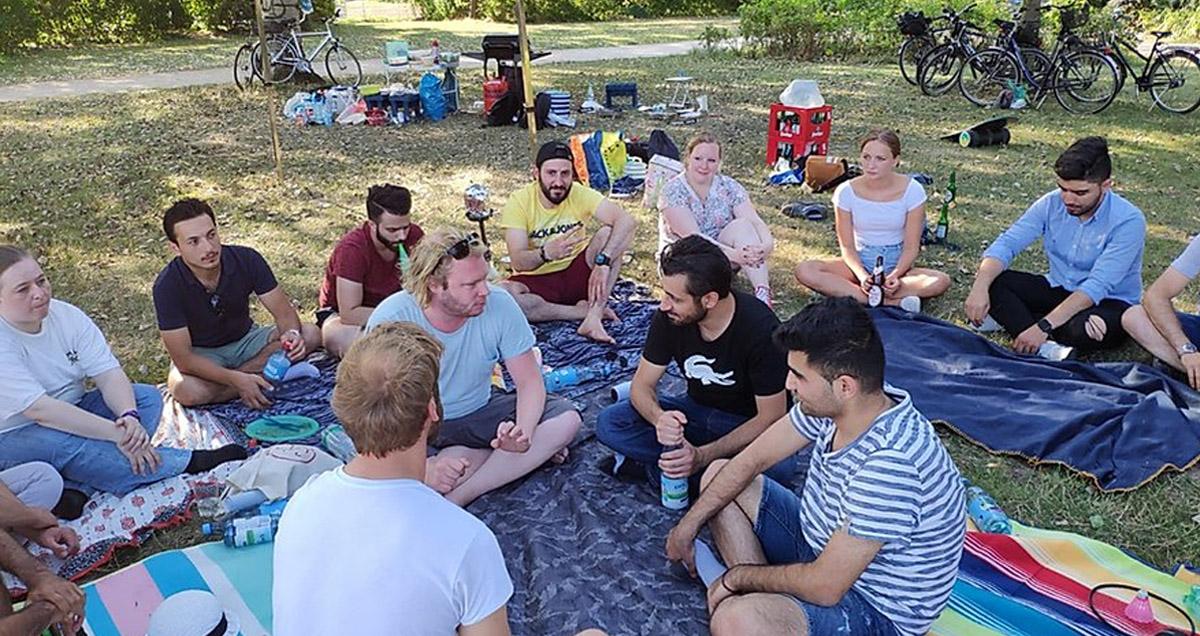 Foto: Gruppe von Teilnehmer sitzt auf einer Decke im Park