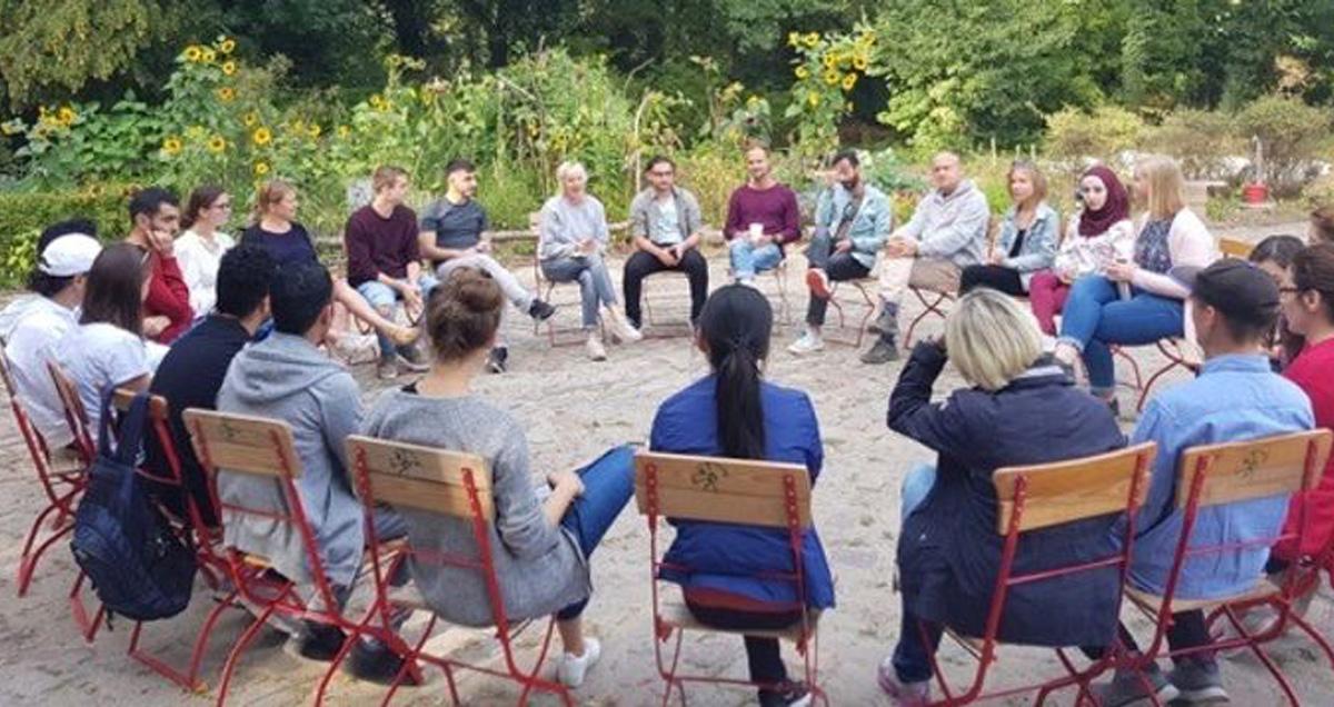 Foto: Teilnehmer sitzen in einem Stuhlkreis im Park