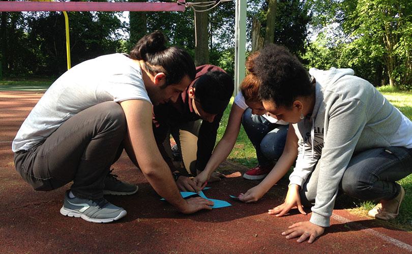 Foto: Eine Kleingruppe erarbeitet im Freien die Teambuilding-Aufgabe mehrere Papierschnipsel zu einem Dreieck zusammen zu legen.